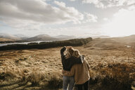 UK, Scotland, Loch Lomond and the Trossachs National Park, rear view of female friends looking at view - LHPF00570
