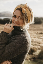 UK, Scotland, Loch Lomond and the Trossachs National Park, portrait of smiling young woman in rural landscape - LHPF00573
