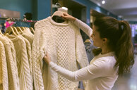 Woman holding a pullover in a vintage boutique - MGOF04001