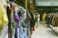 Woman shopping for clothes in a vintage boutique - MGOF04004