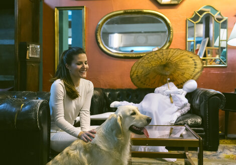 Smiling woman with dog sitting on couch in a vintage shop - MGOF04007