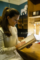 Woman reading an old book in a vintage shop - MGOF04016