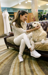 Happy woman with dog sitting on couch in a vintage shop - MGOF04025