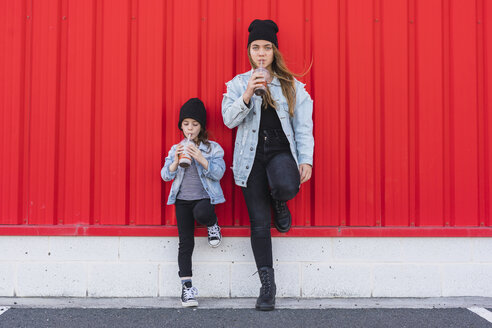 Teenage girl and little sister leaning against red wall drinking cocoa - ERRF01145