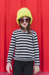 Portrait of astonished little girl wearing striped shirt, yellow cap and oversized sunglasses - ERRF01169