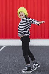 Little girl wearing striped shirt and yellow cap balancing - ERRF01172