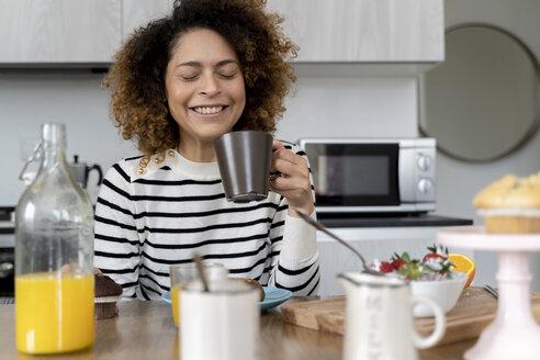Woman sitting in kitchen, having breakfast - FMOF00589