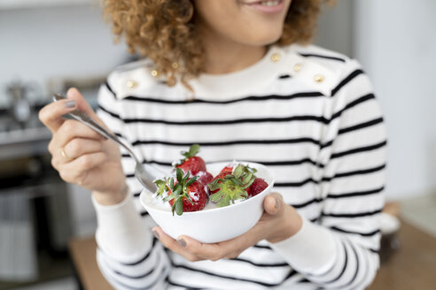 Woman eating strawberries at home - FMOF00592