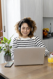 Woman sitting at table, using laptop with headphones - FMOF00595