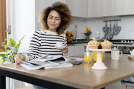 Woman sitting in kitchen, reading magazines and drinking coffee - FMOF00598