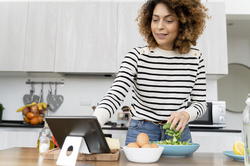 Woman standing in kitchen, preparing salad for lunch - FMOF00604