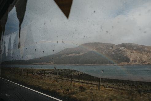 UK, Scotland, Highland, rainbow above the sea seen through car window - LHPF00615