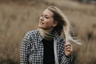 UK, Scotland, Highland, portrait of smiling young woman in rural landscape - LHPF00624
