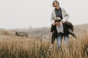 UK, Scotland, Isle of Skye, happy woman carrying friend piggyback in rural landscape - LHPF00627