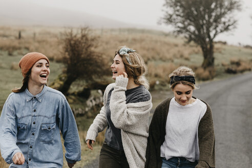 UK, Scotland, Isle of Skye, three happy young woman on a rural road - LHPF00630