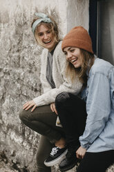 UK, Scotland, two laughing young women at a building - LHPF00633