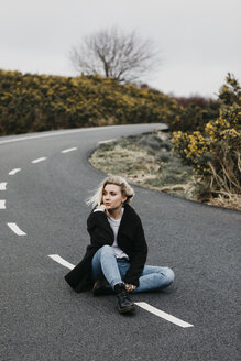 UK, Scotland, Isle of Skye, young woman sitting on country road - LHPF00636