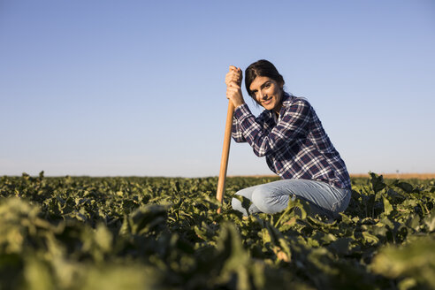 Young woman farmer with hoe on field - ABZF02336