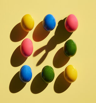 Dyed Easter eggs on yellow background and shadow of bunny ears - KSWF02023