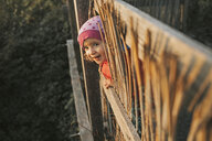 Portrait of smiling toddler girl looking through wooden fence in nature - DWF00394