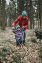 Mother with little daughter and Border Collie in autumnal forest - DWF00403
