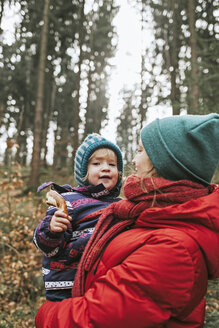 Mother carrying little daughter in autumnal forest - DWF00409