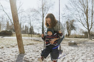 Mother with little daughter on swing on a playground - DWF00415
