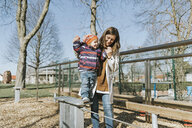 Happy mother with little daughter on a playground - DWF00418