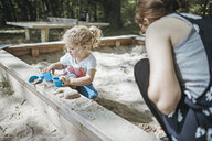 Mother playing with little daughter in sandbox on a playground - DWF00436