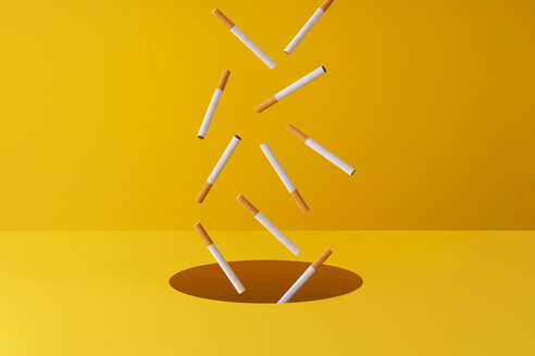 Multiple cigarettes falling into a hole over a yellow background. - DRBF00154