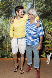 Father and son standing in front of photo wallpaper, having fun - PESF01581