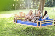 Women of a family relaxing in garden, sitting on a swing bed - PESF01605