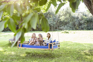 Women of a family relaxing in garden, sitting on a swing bed - PESF01608