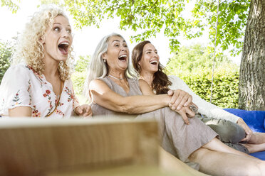 Women of a family relaxing in garden, sitting on a swing bed - PESF01611