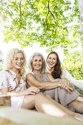 Women of a family relaxing in garden, sitting on a swing bed - PESF01614