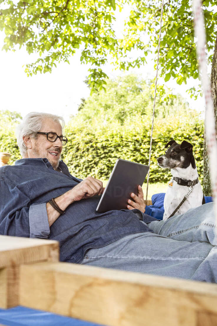 Senior man relaxing on a swing bed in his garden, using digital tablet - PESF01617 - Peter Scholl/Westend61
