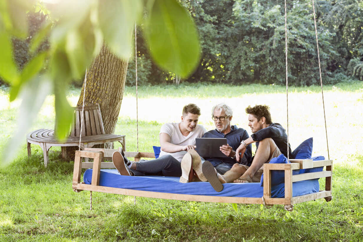 Men of a family sitting on a swing bed ing the garden, talking, using digital tablet - PESF01629 - Peter Scholl/Westend61