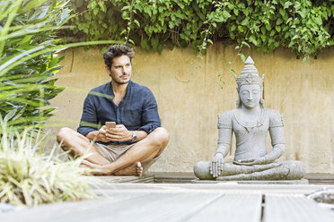 Man sitting cross-legged next to Buddha statue in a Zen garden, using smartphone - PESF01632
