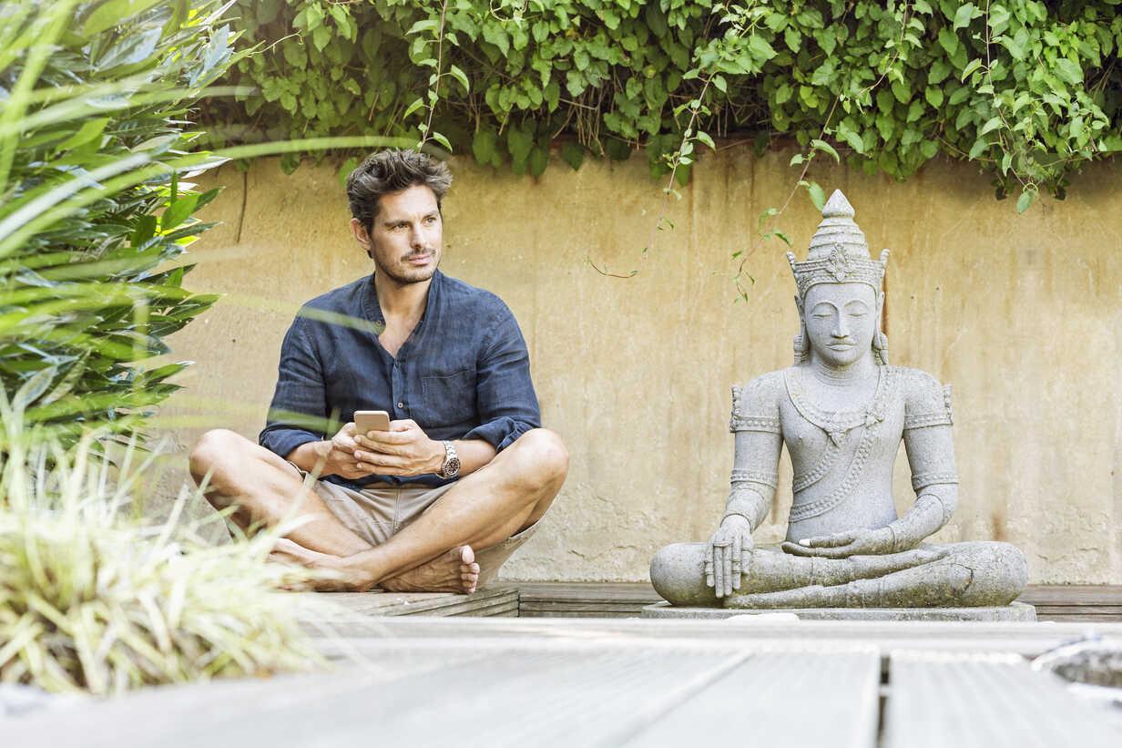 Man sitting cross-legged next to Buddha statue in a Zen garden, using smartphone - PESF01632 - Peter Scholl/Westend61