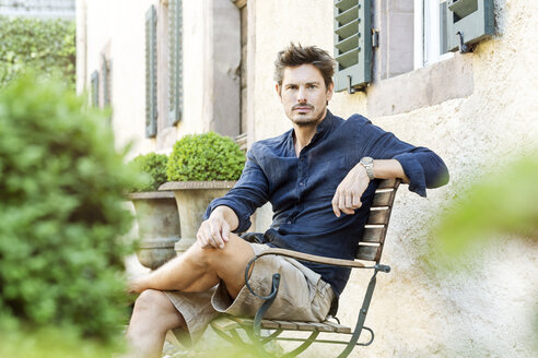 Mid adult man sitting in his lush garden - PESF01635