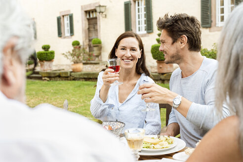 Happy family eating together in the garden, clinking glasses - PESF01647