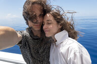 Seychelles, Indian Ocean, mature couple taking selfie on ferry - NDF00905