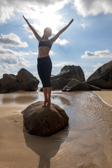 Seychelles, Mahe, Takamaka Beach, woman doing yoga on a rock - NDF00917