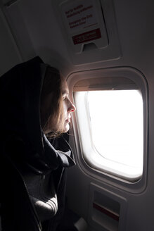 Profile of woman in airplane looking out of window - NDF00923
