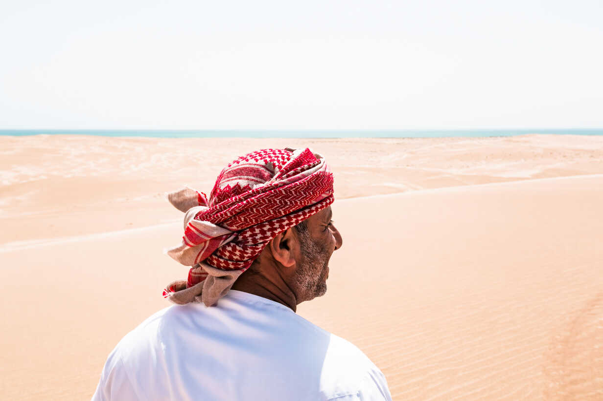 Bedouin in National dress standing in the desert, rear view, Wahiba Sands, Oman - WVF01315 - Valentin Weinhäupl/Westend61