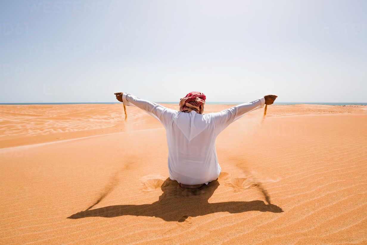 Bedouin in National dress sitting in the desert, holding sand, Wahiba Sands, Oman - WVF01318 - Valentin Weinhäupl/Westend61