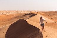 Man walking on a sand dune, Wahiba Sands, Oman - WVF01354