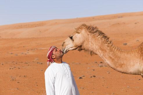 Bedouinn kisses his camel in the desert, Wahiba Sands, Oman - WVF01363