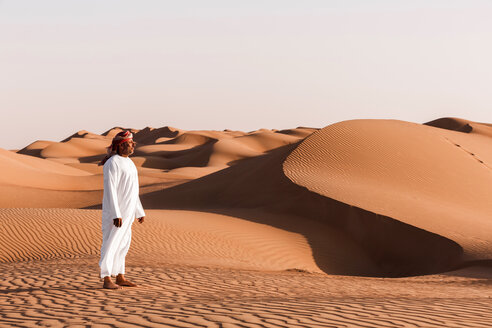 Bedouin in National dress standing in the desert, Wahiba Sands, Oman - WVF01378
