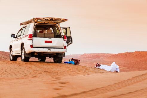 Bedouin taking a break next to his car in he desert, Wahiba Sands, Oman - WVF01408